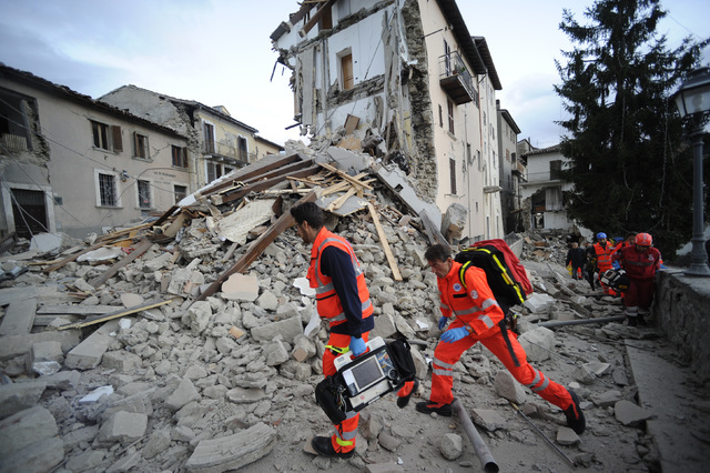 Rescuers search a crumbled building in Arcuata del Tronto, central Italy, where a 6.1 earthquake struck just after 3:30 a.m., Wednesday, Aug. 24, 2016. (Sandro Perozzi/AP)