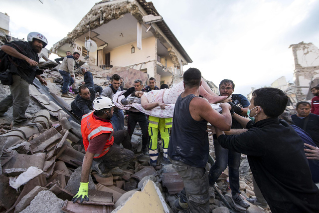 A woman is pulled out of the rubble following an earthquake in Amatrice Italy, Wednesday, Aug. 24, 2016.  The magnitude 6 quake struck at 3:36 a.m. (0136 GMT) and was felt across a broad swath of  ...