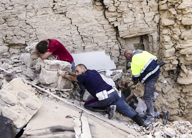 A man cries as another injured is helped in Amatrice, central Italy, where a 6.1 earthquake struck just after 3:30 a.m., Wednesday, Aug. 24, 2016. The quake was felt across a broad section of cent ...