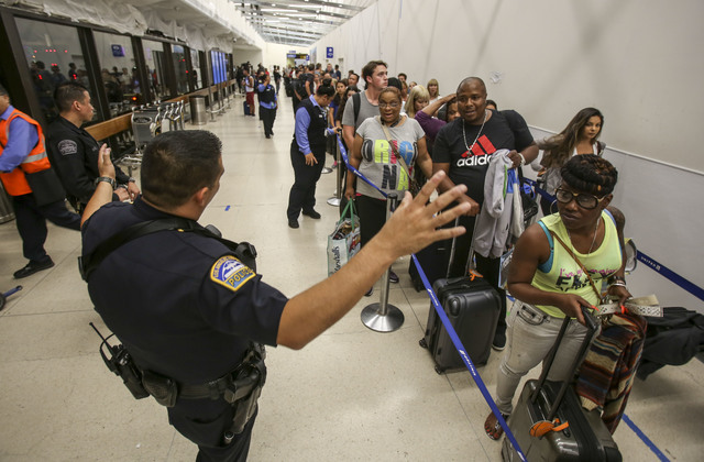 Police officers stand guard as passengers wait in line at Terminal 7 in Los Angeles International Airport, Sunday, Aug. 28, 2016. Reports of a gunman opening fire that turned out to be false cause ...
