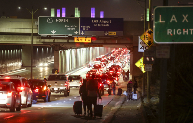 Passengers pull their luggage and walk toward Los Angeles International Airport, Sunday, Aug. 28, 2016. Reports of a gunman opening fire that turned out to be false caused panicked evacuations at  ...