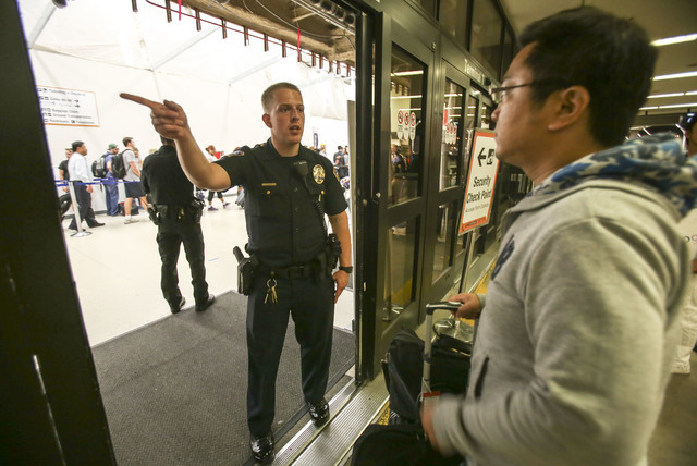 A police officer directs a passenger at Terminal 7 in Los Angeles International Airport, Sunday, Aug. 28, 2016. Reports of a gunman opening fire that turned out to be false caused panicked evacuat ...