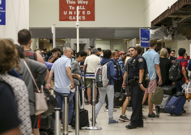 A police officer stands guard as passengers wait in line at Terminal 7 in Los Angeles International Airport, Sunday, Aug. 28, 2016. Reports of a gunman opening fire that turned out to be false cau ...