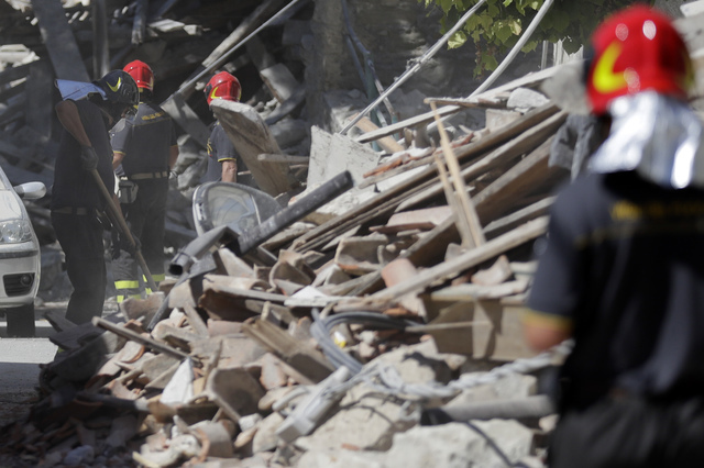 Firefighters work to clear a street from debris in Peschiera Del Tronto, central Italy, Monday, Aug. 29, 2016. Italian authorities are pondering how to provide warmer, less temporary housing for q ...
