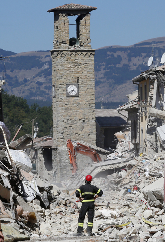 A firefighter stands amid rubble as he watches the bell tower of Amatrice, central Italy, Monday, Aug. 29, 2016. Italian authorities are pondering how to provide warmer, less temporary housing for ...