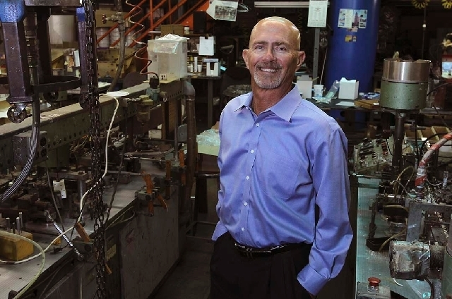 Cary Fisher, President and co-owner of the Fisher Space Pen Co, poses Aug. 6 for a portrait next to a couple of his refill assembly machines at his company's manufacturing plant and headquarters  ...