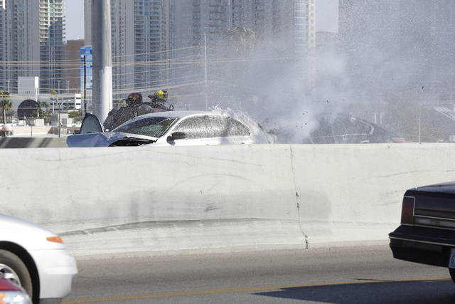 Las Vegas firefighters put out two car fires on Interstate 15 on Monday. The Two vehicles caught fire following a crash northbound between Sahara Avenue and Charleston Boulevard. (Bizuayehu Tesfay ...
