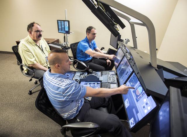 Instructor Michal Rinaldi, left, go through an abort scenario with pilots Carlos Lercari, center, and Kurt Campbell at the Allegiant Airlines flight simulator training facility in Las Vegas on Thu ...