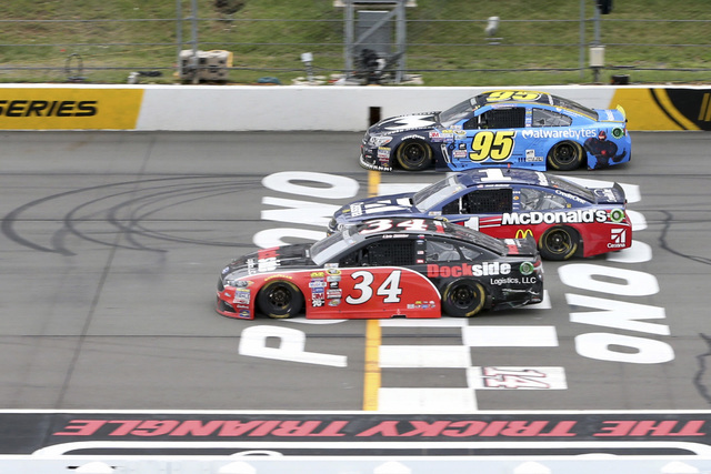 Chris Buescher (34) races with Michael McDowell (95) and Jamie McMurray (1) during the NASCAR Sprint Cup Series Pennsylvania 400 auto race at Pocono Raceway, Monday, Aug. 1, 2016, in Long Pond, Pa ...