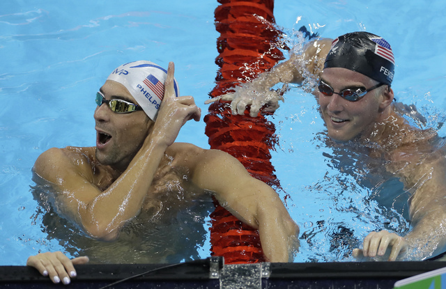 United States' Michael Phelps, left, jokes with his teammate James Feigen during a swimming training session prior to the 2016 Summer Olympics in Rio de Janeiro, Brazil, Tuesday, Aug. 2, 2016. (Ma ...