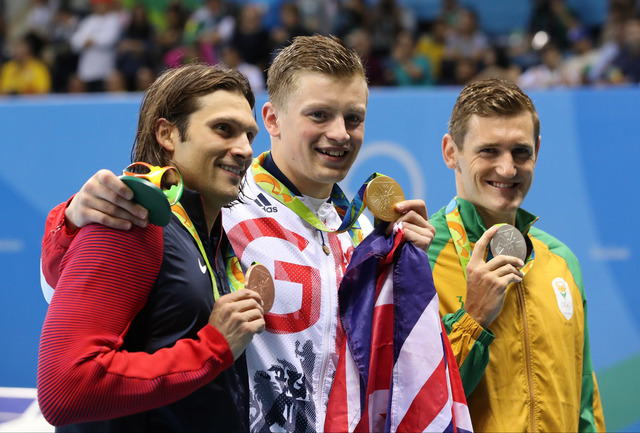 Winner Britain's Adam Peaty, center, second placed South Africa's Cameron Van Der Burgh, left, and third placed United States' Cody Miller hold up their medals after the final of the men's 100-met ...