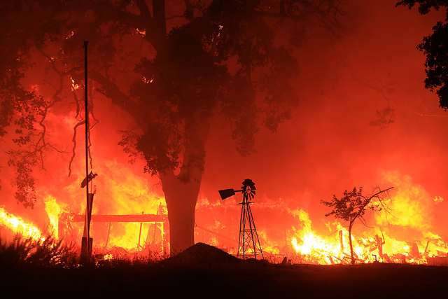 A two-story structure burns in a subdivision off Morgan Valley Road as a wildfire burns in Lower Lake, Calif., Saturday Aug. 13, 2016. More evacuation orders have been issued as the wildfire grows ...
