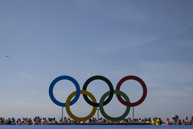 Spectators stand behind the Olympic rings after men's marathon event at the 2016 Summer Olympics in Rio de Janeiro, Brazil, Tuesday, Aug. 16, 2016. (Felipe Dana/AP)