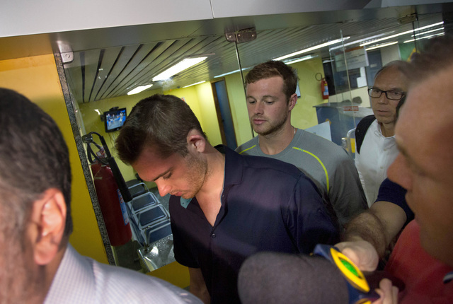American Olympic swimmers Gunnar Bentz, center left, and Jack Conger, center right, leave the police station at Rio International airport early Thursday Aug. 18, 2016. The two were taken off their ...