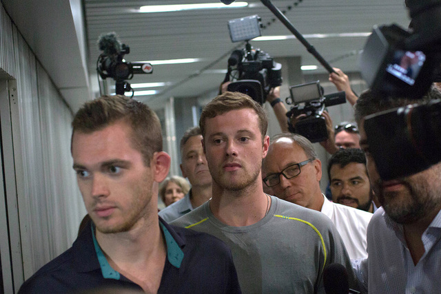 Journalists surround American Olympic swimmers Gunnar Bentz, left, and Jack Conger, center, as they leave the police station at Rio International airport early Thursday Aug. 18, 2016. The two were ...