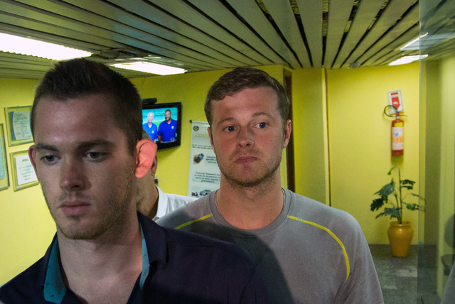 American Olympic swimmers Gunnar Bentz, left, and Jack Conger, center, leave the police station at Rio International airport early Thursday Aug. 18, 2016. The two were taken off their flight from  ...