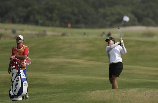 Inbee Park, a Bishop Gorman product, hits to the ninth green as her caddie Bradley Beecher looks on at the 2016 Summer Olympics in Rio de Janeiro, Friday, Aug. 19, 2016. (Alastair Grant/AP)