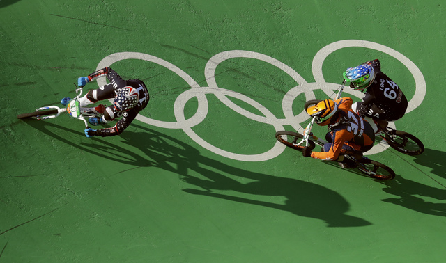 Connor Fields of the United States, left, leads in the last turn before the finish line to win gold in in the men's BMX cycling final followed by Jelle van Gorkom of the Netherlands, center, and N ...