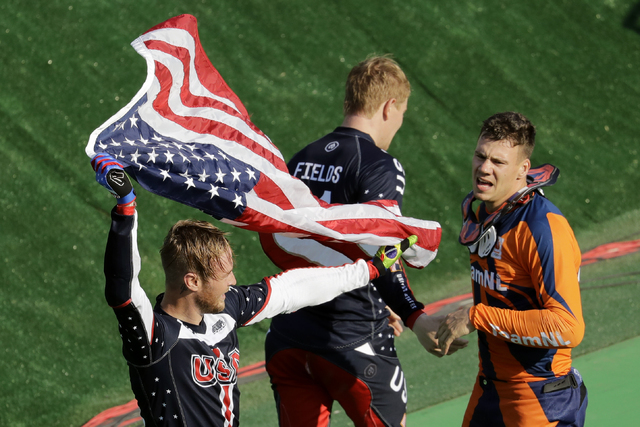Third placed Nicholas Long of the United States, left, waves a U.S. flag next to second placed Jelle van Gorkom of the Netherlands, right, and first placed Connor Fields of the United States, cent ...