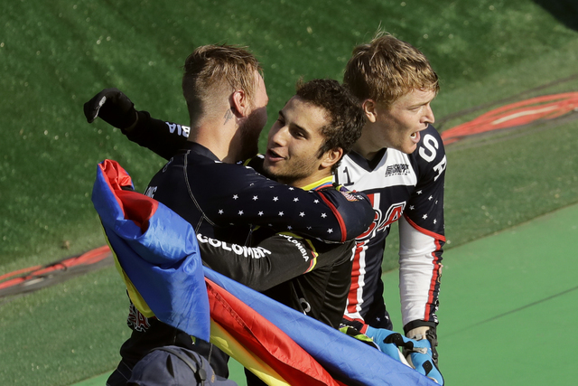 Third placed Carlos Ramirez Yepes of Colombia, center, hugs second placed Nicholas Long of the United States, left, as first placed Connor Fields of the United States, right, stands by them after  ...