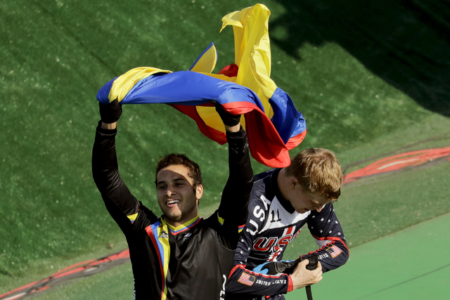 Third placed Carlos Ramirez Yepes of Colombia, left, waves a Colombian flag next to first placed Connor Fields of the United States after the men's BMX cycling final during the 2016 Summer Olympic ...