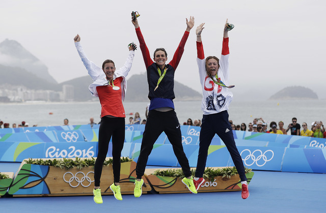 Gold medalist Gwen Jorgensen, of the United States, center, jumps in the air with silver medalist Nicola Spirig Hug, of Switzerland, left, and bronze medalist Vicky Holland, of Great Britain, afte ...