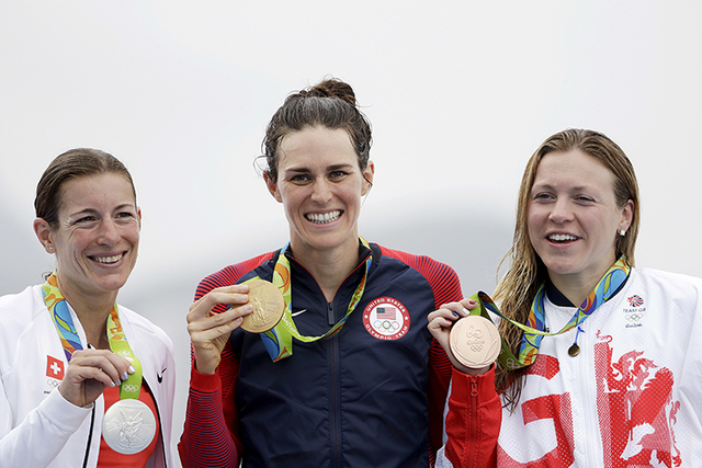 Gold medalist Gwen Jorgensen, of the United States, center, poses with silver medalist Nicola Spirig Hug, of Switzerland, left, and bronze medalist Vicky Holland, of Great Britain, after they comp ...