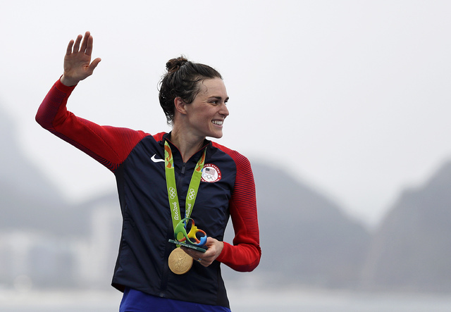 Gwen Jorgensen, of the United States, waves after receiving the gold medal for winning the women's triathlon event on Copacabana beach at the 2016 Summer Olympics in Rio de Janeiro, Brazil, Saturd ...