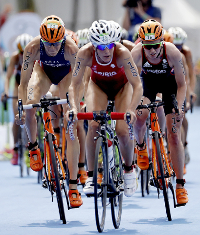 Nicola Spirig Hug, of Switzerland, center, leads Gwen Jorgensen, of the United States, left, and Non Stanford, of Great Britain, right, during the bike portion of the women's triathlon event on Co ...