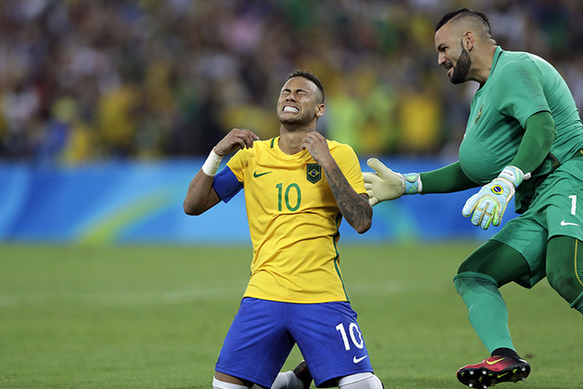 Brazil's Neymar cries as he kneels down to celebrate with teammate goalkeeper Weverton after scoring the decisive penalty kick during the final match of the men's Olympic football tournament betwe ...
