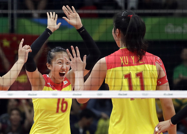 China's Ding Xia, left, celebrates with teammate Xu Yunli during a women's gold medal volleyball match against Serbia at the 2016 Summer Olympics in Rio de Janeiro, Brazil, Saturday, Aug. 20, 2016 ...