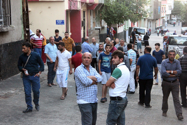 People gather to view damage just hours after Saturday's bomb attack in Gaziantep, southeastern Turkey, early Sunday, Aug. 21, 2016, targeting an outdoor wedding party in southeastern Turkey kille ...