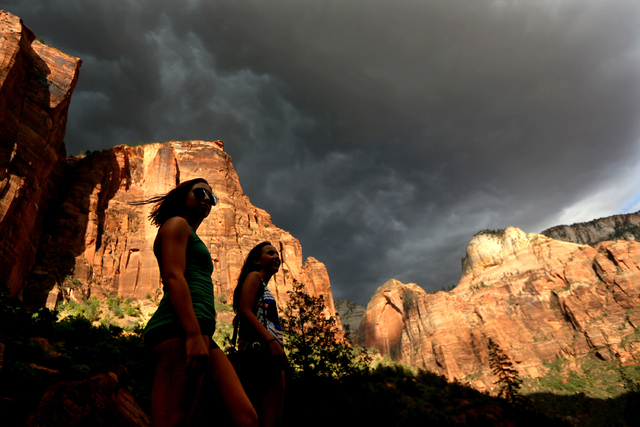 In this Monday, July 22, 2013, file photo, hikers look up at a fast moving storm as it makes its way through Zion National Park outside of Springdale, Utah. Both Zion and Bryce were formed million ...