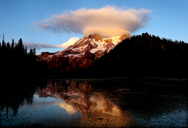 In this September 2012, file photo, a cloud hovers over Mount Rainier at sunset in a view from Klapatche Park Camp at Mount Rainier National Park, Wash. An active volcano, Mount Rainier is the mos ...