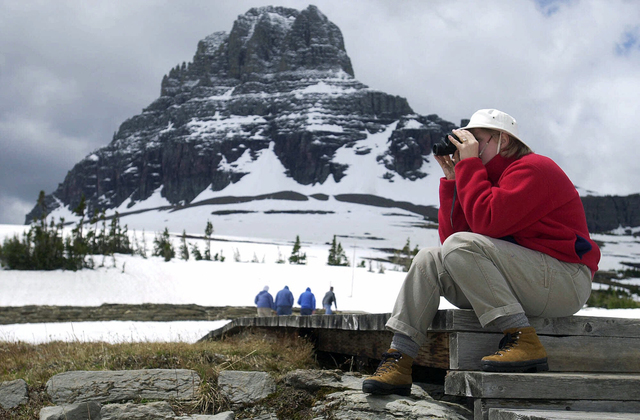 In this June 7, 2001, file photo, Brigitte Pentek, of Lewisburg, W.Va., uses binoculars to watch a gopher while waiting for her husband on one of the trails near Logan's Pass at Glacier National P ...