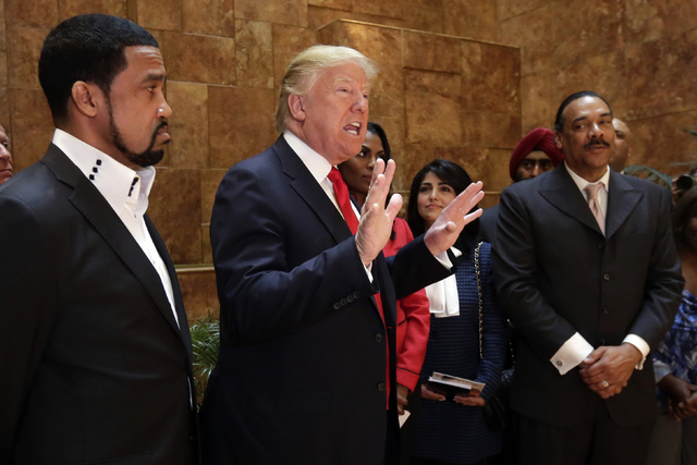 Pastor Darrell Scott listens at left as Republican presidential candidate Donald Trump speaks in Trump Tower building in New York. Competing appearances earlier this month by Trump and Clinton hig ...