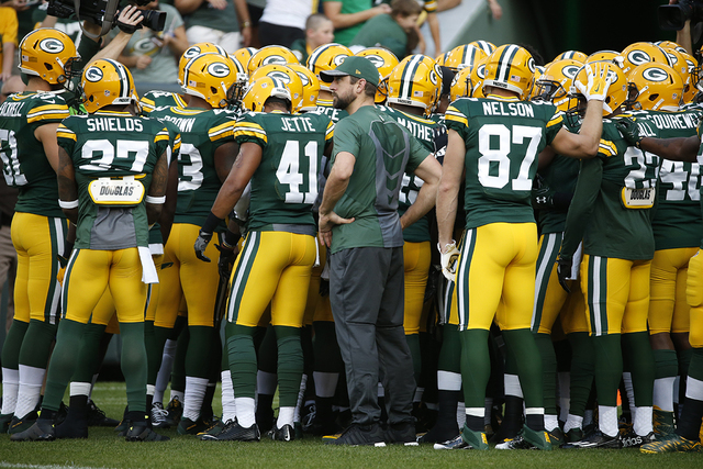 Green Bay Packers quarterback Aaron Rodgers (12) listens to the huddle before an NFL preseason football game against the Oakland Raiders in Green Bay, Wis., Thursday, Aug. 18, 2016. (Mike Roemer/AP)