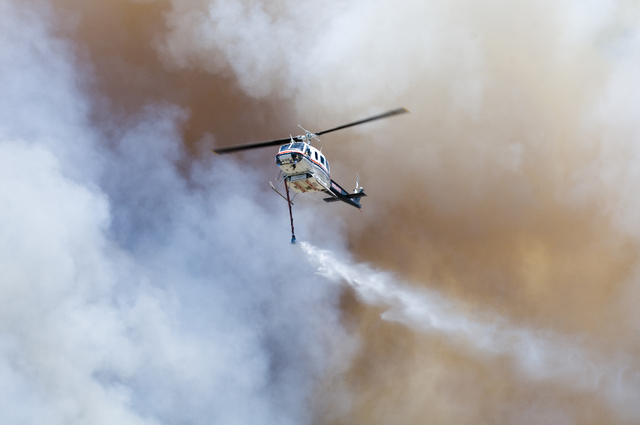 A Helicopter prepares to drop water on a wildfire as it burns near Cajon Pass in California, Tuesday, Aug. 16, 2016. The fire forced the shutdown of a section of Interstate 15, the main highway be ...