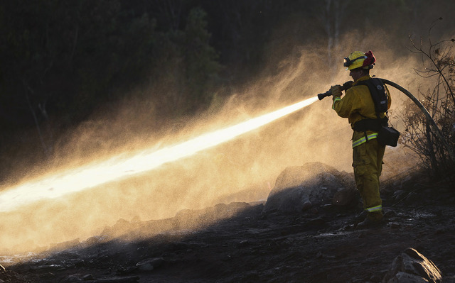 Cal Fire firefighter Jorge Rivera hoses the remaining hot spots left from a brushfire in Spring Valley, Calif., Wednesday, Aug. 17, 2016. (Hayne Palmour IV/The San Diego Union-Tribune via AP)