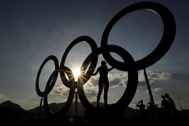 A woman poses for a photo with the Olympic Rings at the Olympic Park in Rio de Janeiro, Brazil, Monday, Aug. 1, 2016. The Summer 2016 Olympics opens Friday, Aug. 5. (Charlie Riedel/AP)