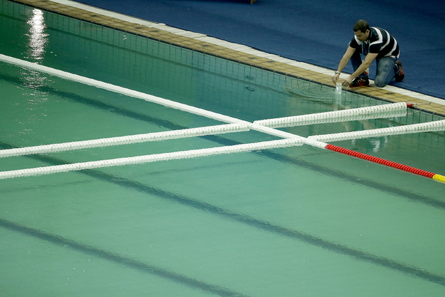 An inspector takes a sample from the water polo pool which turned green in color today in the Maria Lenk Aquatic Center at the 2016 Summer Olympics in Rio de Janeiro, Brazil, Wednesday, Aug. 10, 2 ...