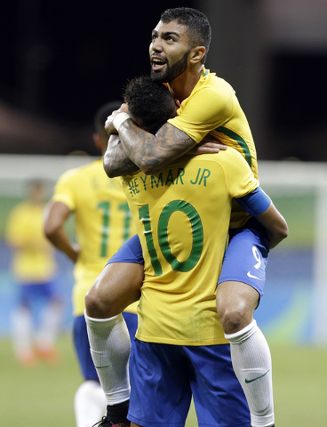 Brazil's Gabriel Barbosa, center, celebrates with teammate Neymar after scoring his team's first goal during a group A match of the men' s Olympic football tournament between Brazil and Denmark in ...