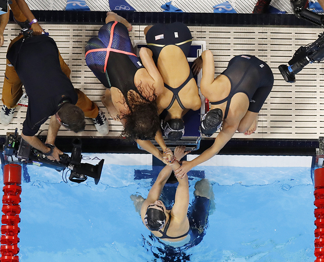United States' Katie Ledecky is congratulated by teammates after winning the gold medal in the 4 x 200m freestyle relay finals during to the swimming competitions at the 2016 Summer Olympics, Thur ...