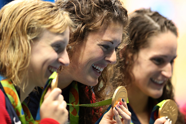The United States team, Katie Ledecky, Allison Schmitt, and Leah Smith hold up their gold medals after winning the women's 4x200-meter freestyle relay during the swimming competitions at the 2016  ...