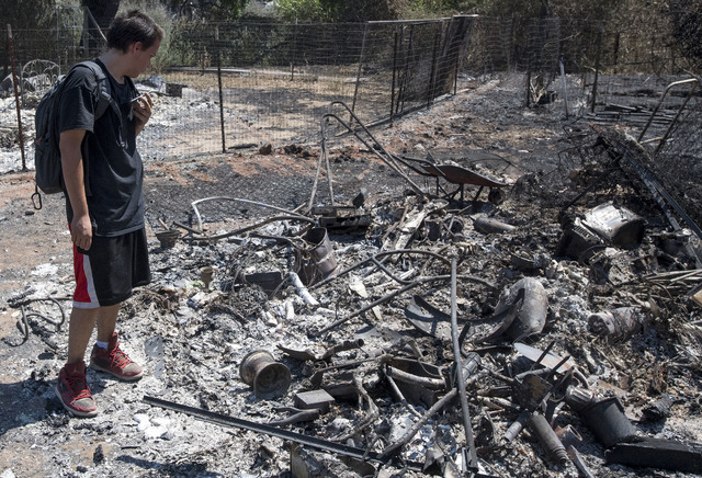 Daniel Brown uses a chat app with his mother while surveying damage to his home after a fire tore through his neighborhood in Lower Lake, Calif., Tuesday, Aug. 16, 2016. (AP Photo/Josh Edelson)