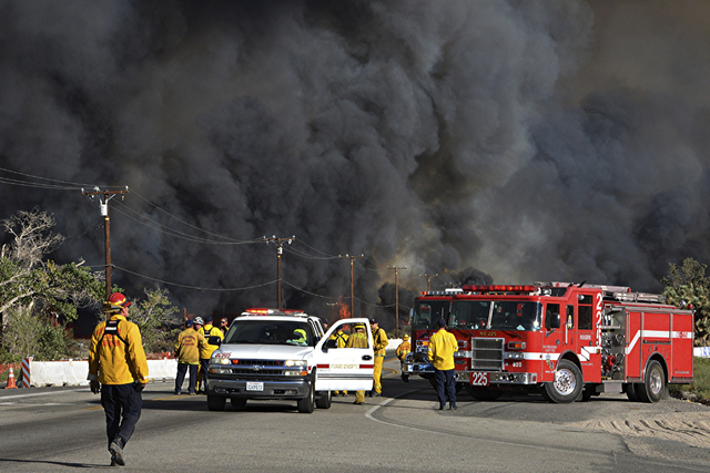 This Tuesday, Aug. 16, 2016 photo Heavy fire envelopes Hwy 138 at Hess Rd in Phelan, Calif. as firefighters prepare to battle a wildfire spreading through San Bernardino County. (AP Photo/Rick McC ...