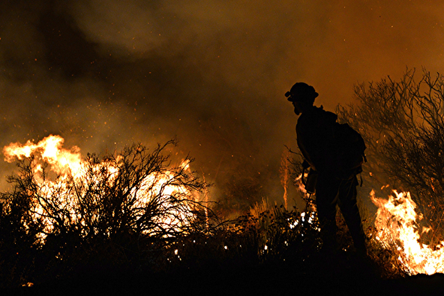Cal Fire firefighter sets a backfire as he is silhouetted against the fire on Lone Pine Canyon Rd. in Wrightwood, Calif. early Wednesday, Aug. 17, 2016. Officials in charge of the battle against C ...