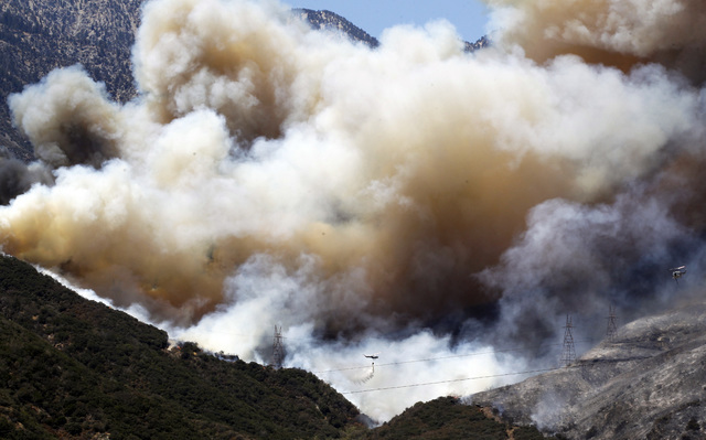 A helicopter drops fire retardant and water over the BlueCut fire in the Cajon Pass near San Bernardino, Calif., Wednesday, Aug. 17, 2016. A wildfire with a ferocity never seen before by veteran C ...