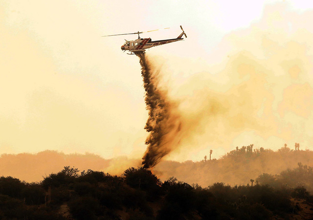 A helicopter makes a drop over a wildfire in West Cajon Valley, Calif., Wednesday, Aug. 17, 2016. A day after the fire ignited in brush left tinder-dry by years of drought, the flames advanced des ...