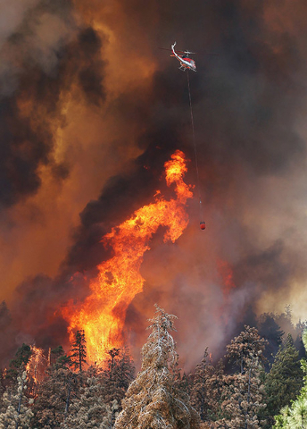 A firefighting helicopter makes water drops on a wildfire in the Greenhorn Mountains off Highway 155, Wednesday, Aug. 17, 2016, west of Wofford Heights, Calif. (Casey Christie/The Bakersfield Cali ...
